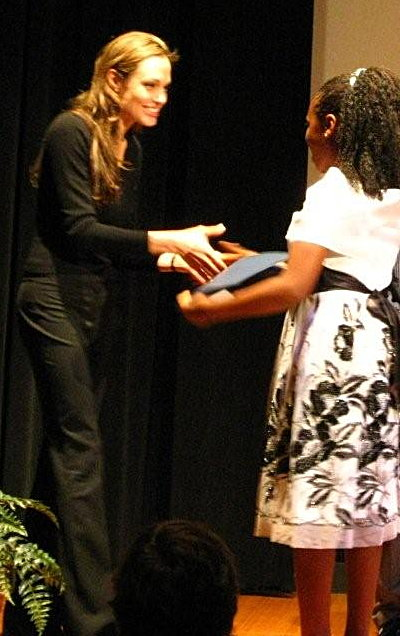 Angelina Jolie congratulates a winner of her poster contest at the World Refugee Day event at the National Geographic Museum in Washington, D.C.