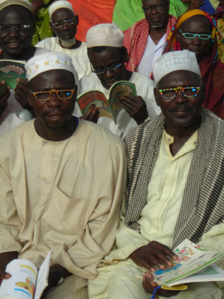 Darfuri men trying new reading glasses in Chad